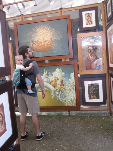 man with baby in back pack carrier looking at paintings