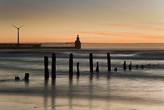 Blyth | Dawn (Reed Ingram Weir) Tags: longexposure light orange seascape cold sunrise prime dawn pier sticks warm waves hyperfocal 85mm bank northumberland northeast windturbine blyth ofcloud reedingramweirriwp