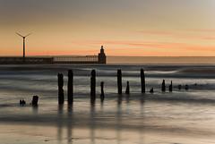 Blyth | Dawn (Reed Ingram Weir) Tags: longexposure light orange seascape cold sunrise prime dawn pier sticks warm waves hyperfocal 85mm bank northumberland northeast windturbine blyth ofcloud reedingramweirriwp