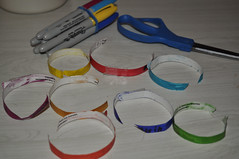 picture of all the cut off paper collars on the counter with the sharpies and scissors behind them