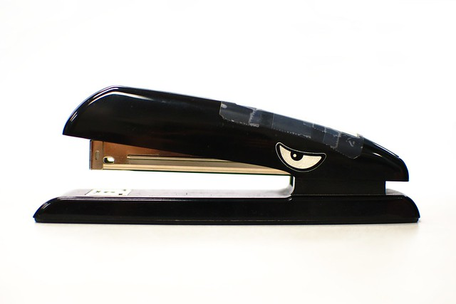 A stapler with an eye and alligator teeth.