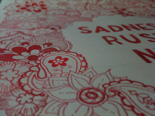 A close up photo of one of my drawings, paisley type shapes and flowers and some cut off text all drawn in red ink.