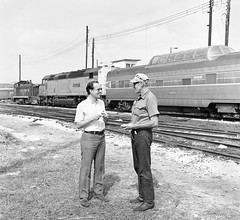 Amtrak's Floridian is in the background at the SCL (former ACL) railroad yard, with SCL electrician Charlie Bruorton & alcomike43, in foreground at Saint Petersburg, Florida, 1975  (Photo by Fred Clark Jr.) (alcomike43) Tags: old blackandwhite bw yard vintage track diesel engine rail historic negative amtrak photograph budd locomotive acl sw9 switcher scl dieselengine passengertrain seaboardcoastline railroadyard emd domecar diesellocomotive dieselelectriclocomotive atlanticcoastline sdp40f amtrakfloridian conventionallightweightpassengercar