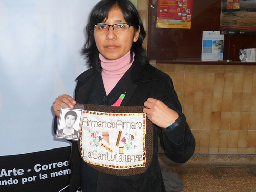 Family member of the disappeared holds up her pastilla with her disappeared brothers name