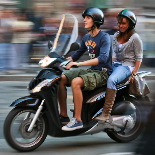 Couple riding a scooter in Bologna, Italy.