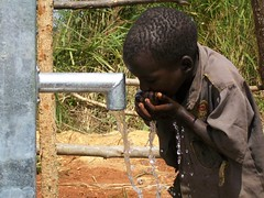 A young boy drinks water straight from the pump