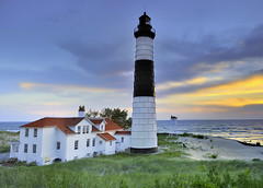 Big Sable Point Lighthouse  (Ludington State Park, Ludington Michigan) (Michigan Nut) Tags: blue light sunset red usa lighthouse seascape color green art beach nature grass clouds reflections bench landscape geotagged photography nikon waves photos dunes lakemichigan explore recent frontpageexplore bigsablelighthouse d700 grandpointausable