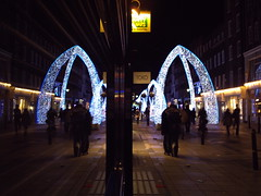 A Pair of Arches, South Molton Street, London, a couple embrace (Cybermyth13) Tags: christmas street xmas uk blue england white reflection london window dark lights evening pair streetphotography 9 arches instruction 2010 londonist southmolton spnp