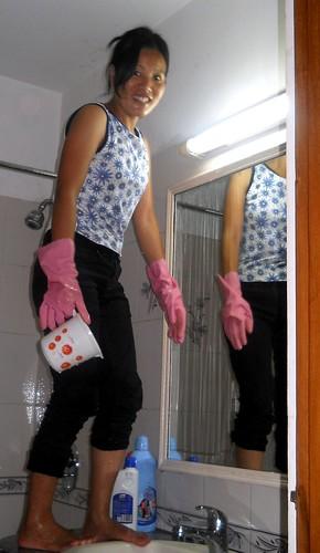 Christina scrubbing walls of bathroom