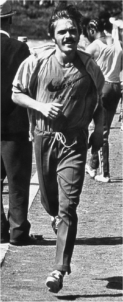 """Steve Prefontaine in Nike Gear running with """"Olympic Trials"""" lettered below the Nike t-shirt logo, July 1972 Olympic Trials Eugene, Oregon"""