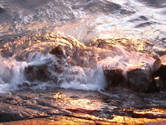the smell of rocks and water, washing over me (ailie*) Tags: light sunset orange sunlight lake motion blur detail water reflections golden movement rocks waves sparkle splash ailie crashing