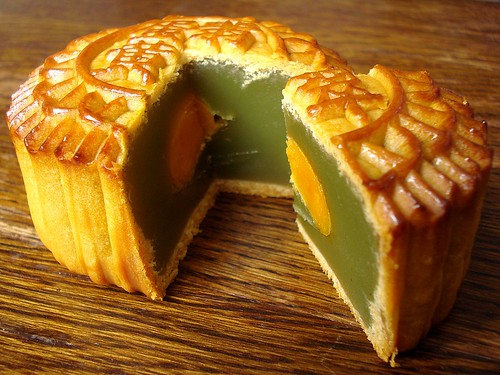 The same pastry as pictured at the top of this post, but sliced into to reveal a dark green paste filling with a bright yellow egg yolk embedded in it.