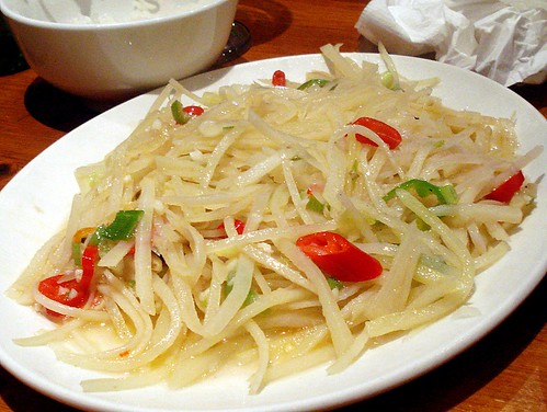 A white plate piled with a heap of potato slivers.  The potatoes are cooked just enough that they have lost their rigidity, but not enough to brown them.  A few pieces of sliced red chilli and spring onion are visible among the potato strands.