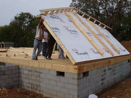 Volunteers at the Self-Help Build Day begin the day by erecting the north end wall of the house.