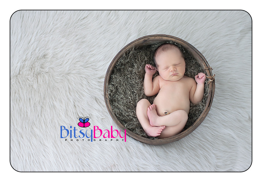 Newborn in wooden bowl