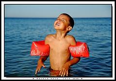 The Boy Who Stare at the Sun - l'Enfant qui regarde le soleil (Rachid Naim) Tags: africa boy man beach water canon la sand kiss eau sable morocco maroc marrakech safi marruecos plage tanger homme garon  afrique  mediteranean       eos450d                 medittrane    rachidnaim