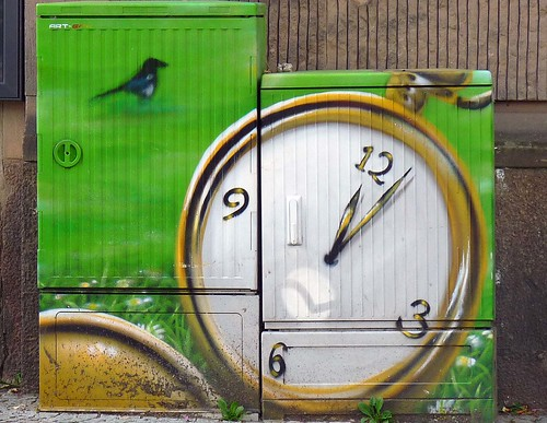 graffiti of a pocket watch (the hands read just past 12 o'clock) on a green background with a bird hovering, seated, just to the upper left