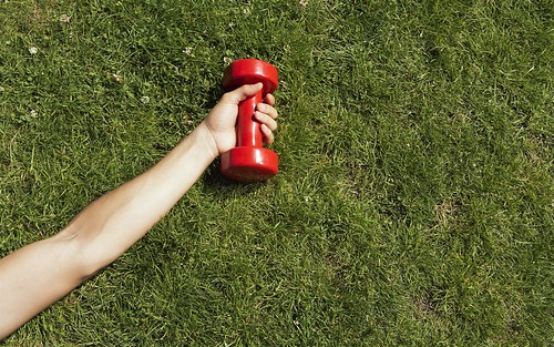Lying in grass with dumbbell