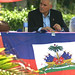 Charles Henri Baker running for President of Haiti sitting on stage with Haitian flag