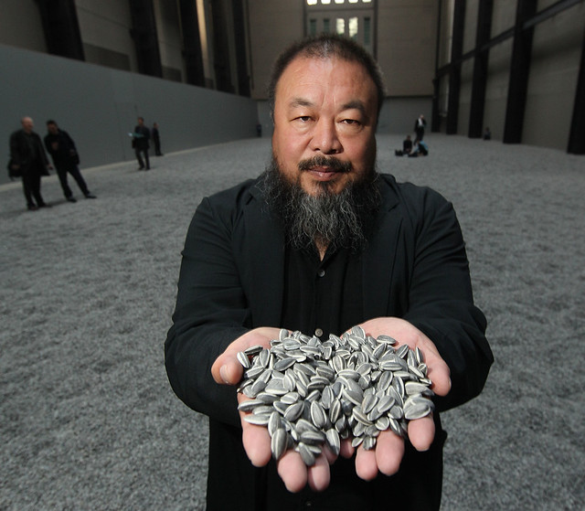 Ai Weiwei holds hand-painted, porcelain sunflower seeds from his installation at the Tate Modern in London.