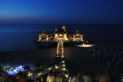Sellin Pier at Night with Beach Party /                                                                                         Nachtaufnahme der Seebrcke Sellin mit Beachparty (chrisshots) Tags: blue sunset summer sky sun colour beach water beautiful architecture night strand stairs buildings germany deutschland lights pier fantastic nikon meer sonnenuntergang dusk tripod bluesky balticsea retro treppe pedestrians romantic omg rgen ostsee beachparty manfrotto nachtaufnahme sellin  onblue mecklenburgvorpommern strandkrbe abendstimmung seebrcke strandparty chrisshots d3000 flickraward tauchglocke qualitypixels lightjunkies panoramafotogrfico seenbymyeyes flickrawardgallery beachchairseebrcke