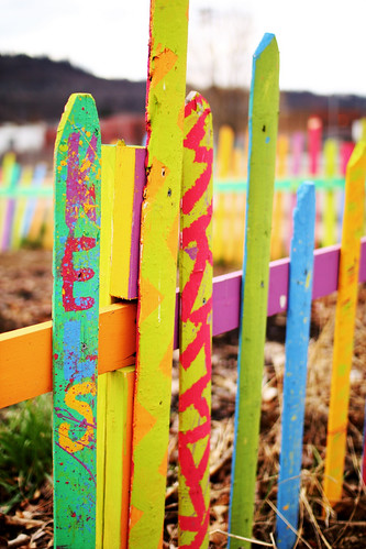 a colorful fence surrounds a garden (by: Ken Schultz, creative commons license)