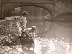 By the canal 2 (Abaraphobia) Tags: bridge family 1920s boy summer portrait england sunlight playing game reflection cute water girl childhood sepia vintage hair children boat canal photo blackwhite thirties 1930s photographer play dress sweet britain sister brother candid snapshot snap adventure nostalgia walkway nostalgic british shorts ripples discovery idyllic barge foundphoto embankment watford waterway smock cassioburypark grandunioncanal foundimage twenties uptonroad watfordfc watfordfootballclub cassioroad bridge163 mreaife ladycapelsbridge