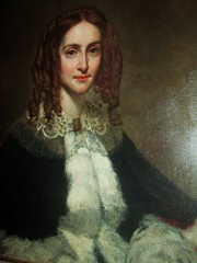 a portrait of a smiling lady from the 1850s with long curls in her hair and a jacket with white fur down the front