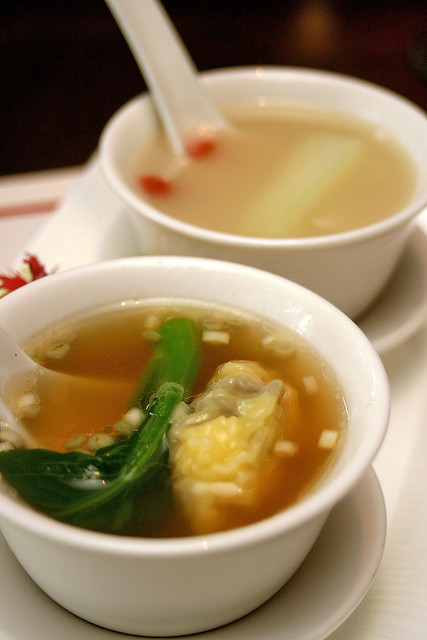 Hong Kong style minced pork and shrimp dumpling soup with choy sum (foreground) and Double-boiled fish broth with pak choy, fish maw and tofu