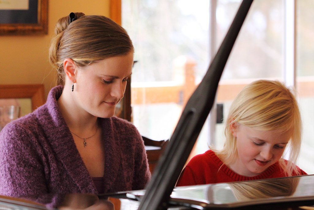 Sara and Emma playing Christmas music on the piano.