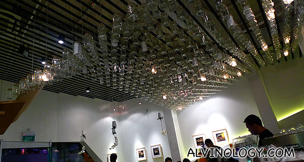 Rows of inverted wine glasses on the ceiling for decor