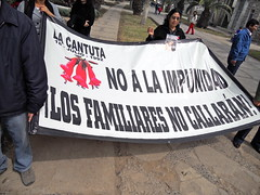Family Member of La Cantuta Victim Holds Poster for Press