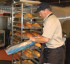 Rich Corson bags up french bread fresh out of the oven at Safeway. As part of its lifestyle remodel, the store will now offer fresh baked French bread at 10 a.m. and 5 p.m. daily.