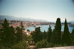 View over Split harbour (KimpyWoo) Tags: trees film analog 35mm landscape lomo lca lomography scenery view harbour croatia 400 analogue filmcamera nophotoshop split nondigital expired 35mmphotography 400iso unedited expiredfilm c41 filmphotography 35mmcamera traditionalphotography vintagephotography c41film truprint400