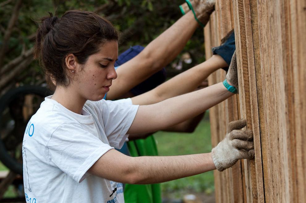 Manos de voluntarios y manos de gente beneficiada con esta campaña colaboran juntos en la colocación de los paneles que forman las paredes de la nueva casa. (Elton Núñez - Asunción, Paraguay)