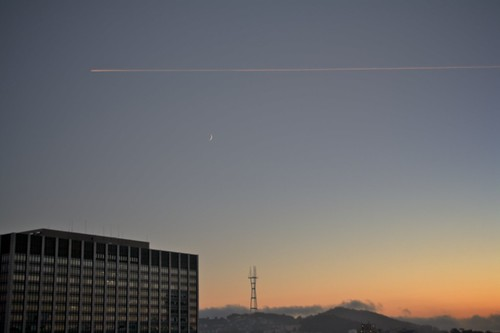 An airplane passes Sutro Tower