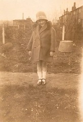 All dressed up! (Abaraphobia) Tags: family 1920s houses england cute english girl smile childhood smiling fashion sepia vintage fence garden happy photo blackwhite thirties 1930s outfit child sweet britain path coat snapshot shed adorable snap dressedup nostalgia dressingup nostalgic british suburbs flapper idyllic loveable foundphoto watford strappyshoes foundimage twenties tinbath furcollar clochehat cassioroad mreaife
