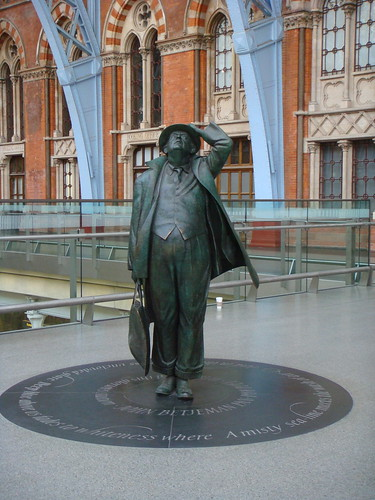 The statue of John Betjeman in St. Pancras station where he holds on to his hat while looking to the sky