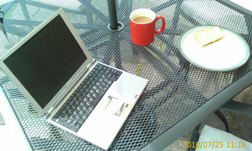 Laptop and working lunch. An outside table with a silver laptop, coffee and a sandwich on it.