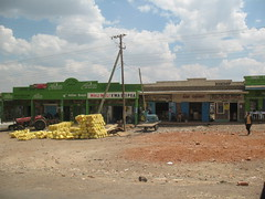 Sam Chemist (aaron.knox) Tags: africa road sky tractor green clouds highway kenya pedestrian powerlines shops cart bookshop fromacar chemist kisii malimali safaricom