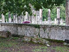Ruins Rain (John Fraissinet) Tags: travel archaeology wall umbrella ruins hidden greece olympia behind olympics pillars johnfraissinet streetobservationscom