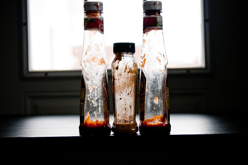 nearly empty sauce bottles