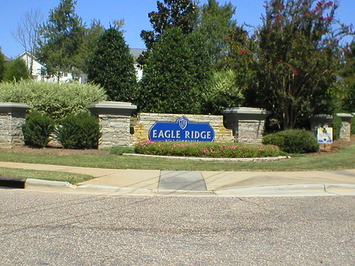stone columns and stone planters with flowers surrounding the entrance sign to Eagle Ridge golf community in Garner, North Carolina from side
