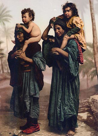 Albumen studio portrait of two Bedouin women with children on their backs taken by Maison Bonfils in ca. 1895 in Syria. PHOTOCHROME FROM ORIGINAL NEGATIVE BY BONFILS [701 BEDOUINES SYRIENNES PORTANT LEURS ENFANTS (1901 CATALOG, P. 51)] Original albumen version, AD2000-326. Penn Museum Image 166009. This image is protected by United States copyright. Please contact the Penn Museum archives for permission to re-distribute this image.