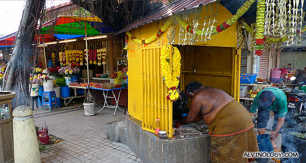 The priest cleaning up the shrine housing a figurine of Ganesh