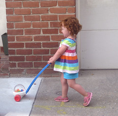 Speck in a colorful shirt pushing her popper down the sidewalk