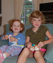 grinning Speck and cousin S, together in an arm chair, with Zuzu pets in hand