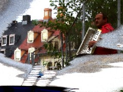 Water art: the busker in a red shirt (peggyhr) Tags: blue friends light red white man reflection green buildings germany puddle grey dresden shadows rooftops pavement drain textures busker accordian parallelworld flipped rainwater moist squeezebox topshots peggyhr artistspotlight 2917a cherryontopphotography flickrsportal temporarywirefence accordiancase