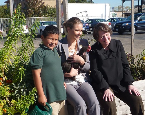 Deputy Secretary Merrigan and Sarah Elizabeth Ippel in the garden at the Academy of Global citizenship with one of their students and a chicken from the school's chicken coop.