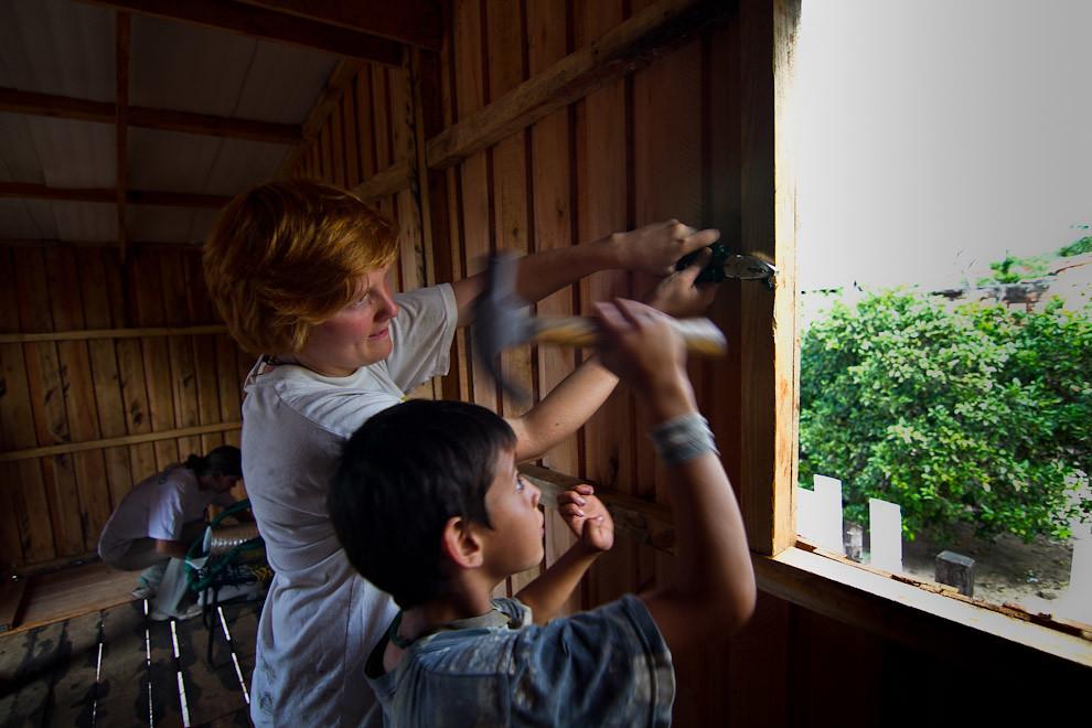 Ayudando a una voluntaria a colocar las bisagras para la ventana. (Tetsu Espósito - Lambaré, Paraguay)